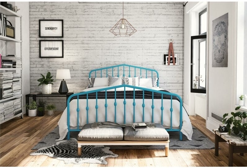 The bed in teal, with slatted wrought-iron-style bars inside a rounded frame at the head and foot of the bed