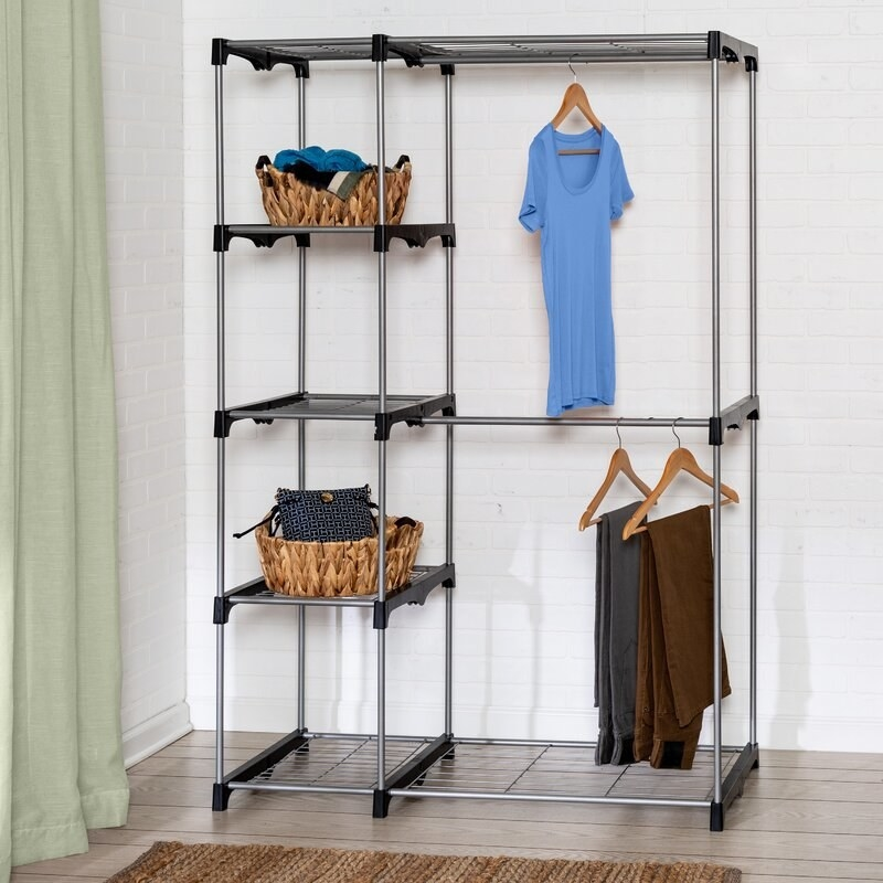 Closet organizer made of metal piping with black plastic brackets, with a top and bottom shelf, 3 shelves on the left side, and two curtain rods with hanging space on the right side