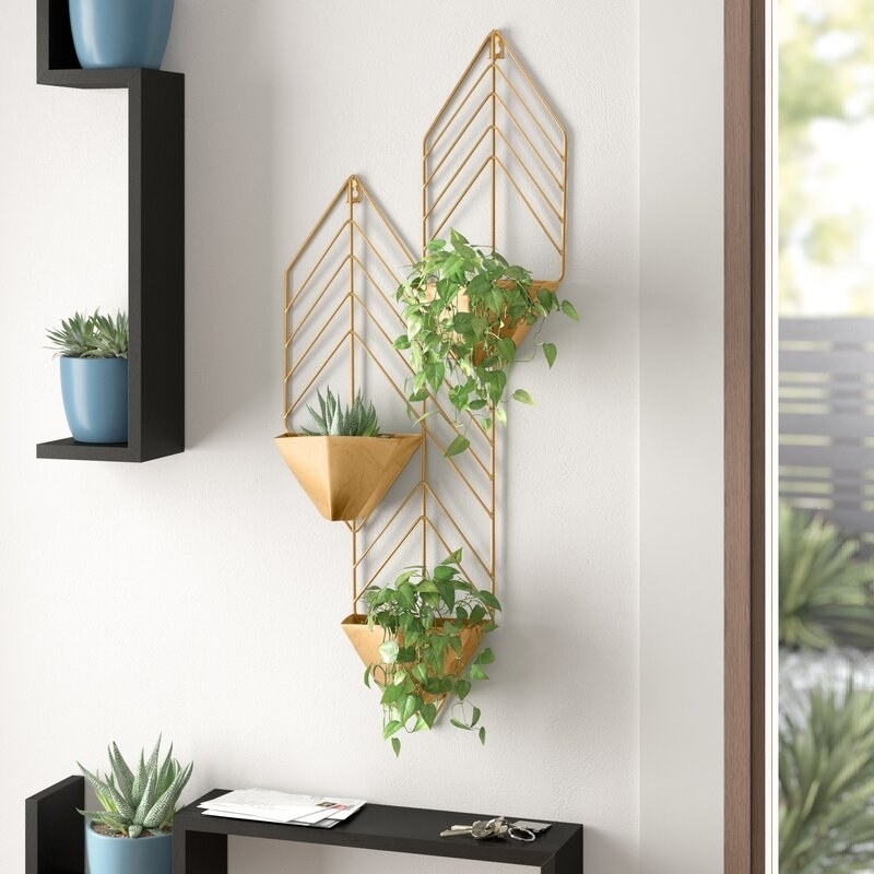 A three-tiered holder with triangular planters jutting out from a chevron-patterened design