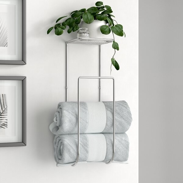 The rack, which is mounted to the wall and has a J shape, with rolled towels fitting inside the curve of the J