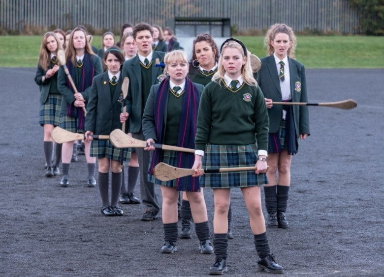 The Derry girls stand with their class holding wooden sports sticks