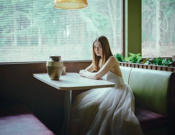 Alyssa sits in a wedding dress at a diner table, looking into the camera