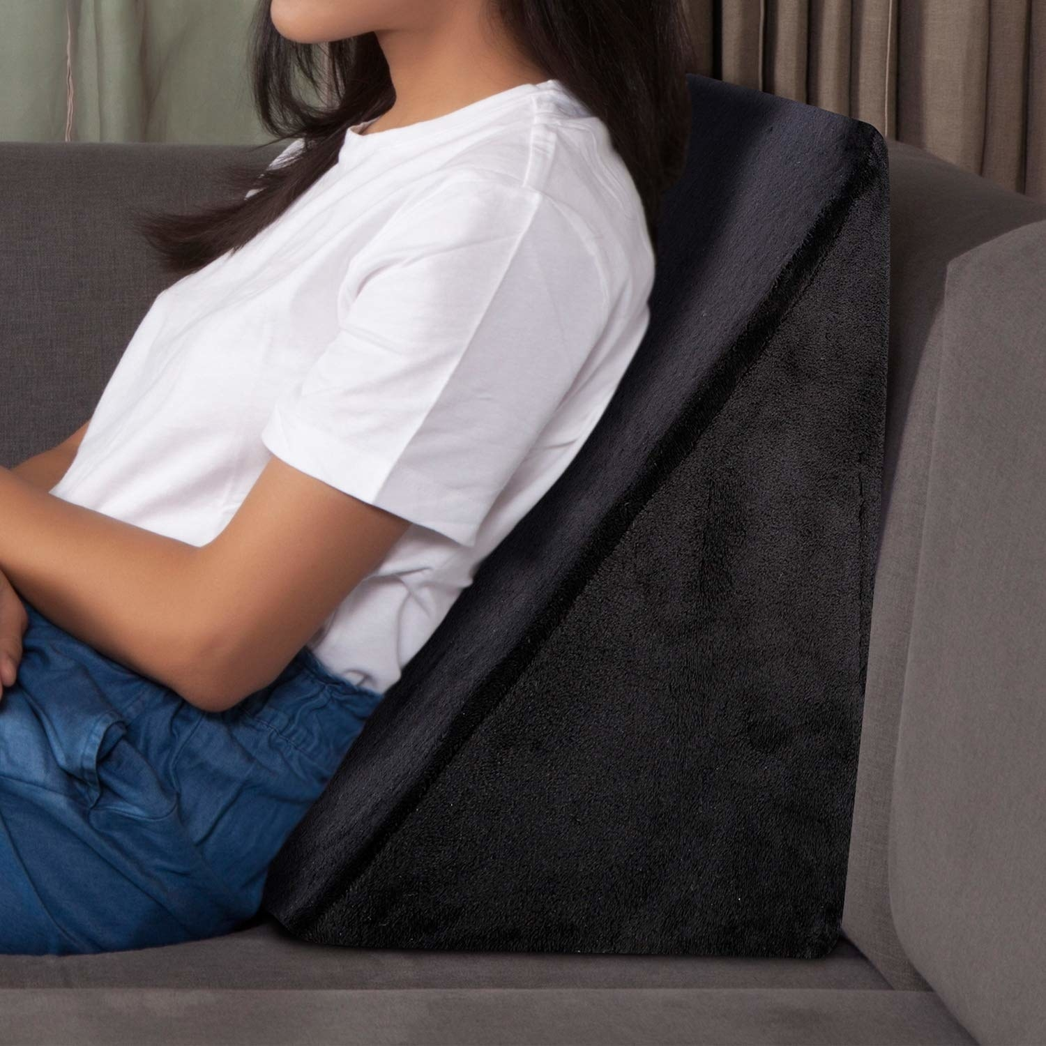 A wedge pillow with a woman leaning on it