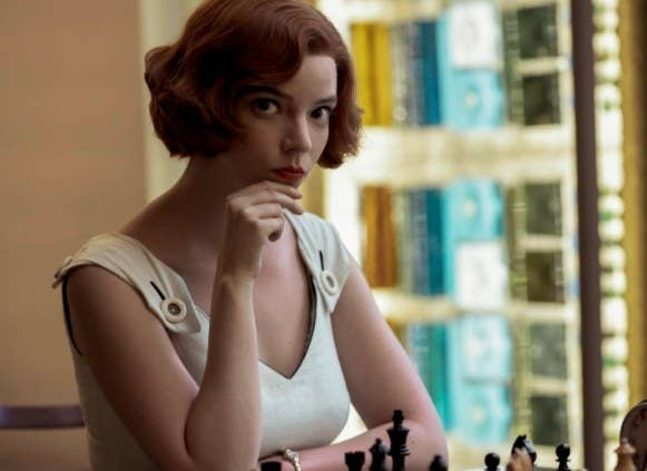 Beth sits in front of a chess set