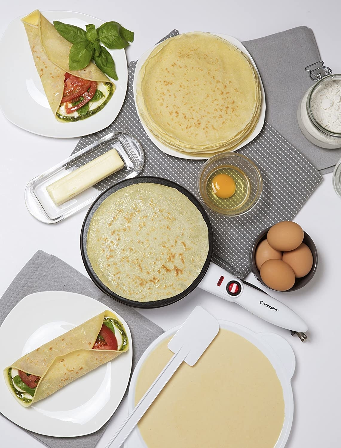 a table with crepe wraps, a plate of batter, eggs, the crepe maker, butter, and some crepes.