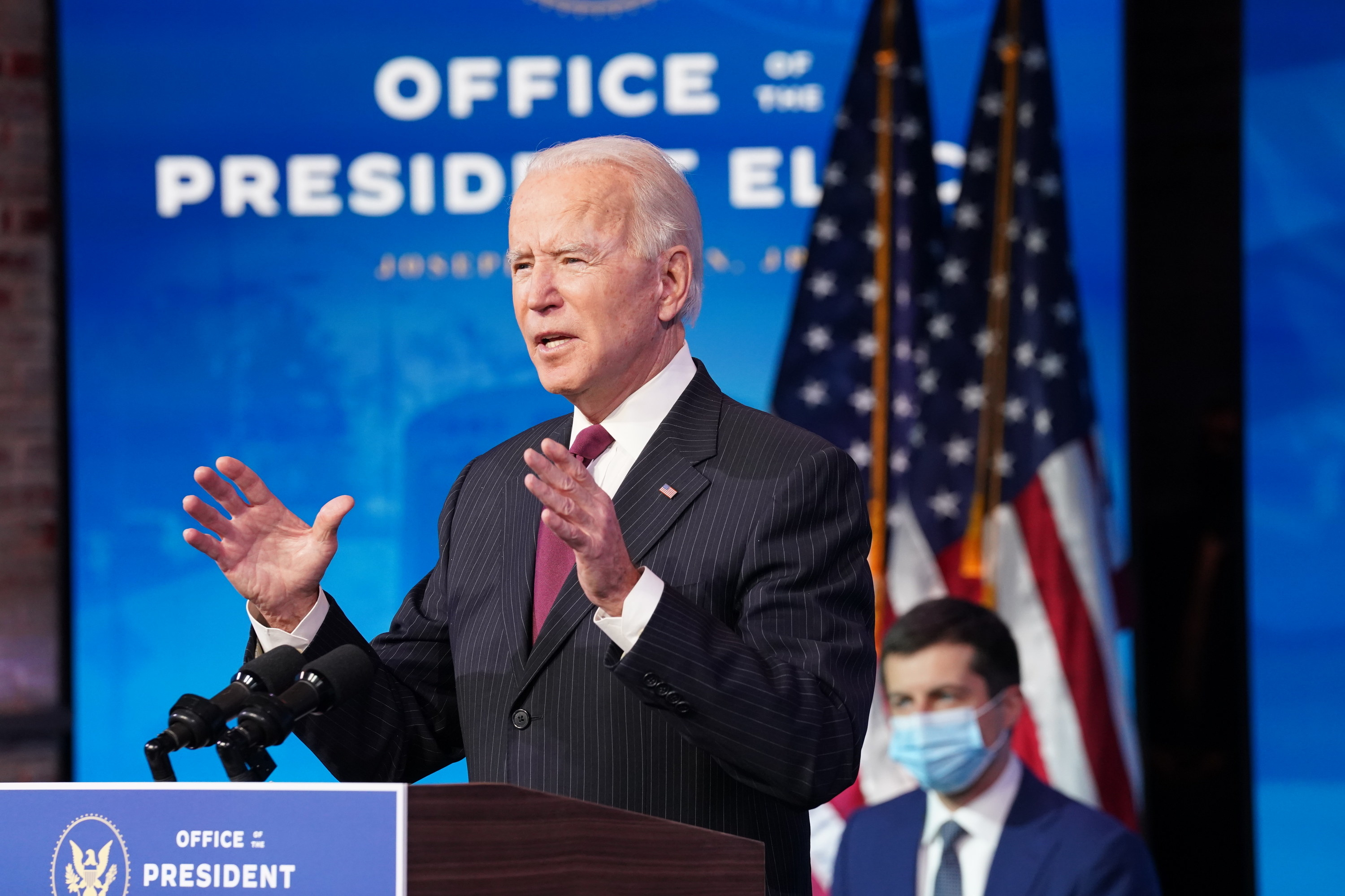 Joe Biden speaks at a podium as Pete Buttigieg sits behind him wearing a face mask