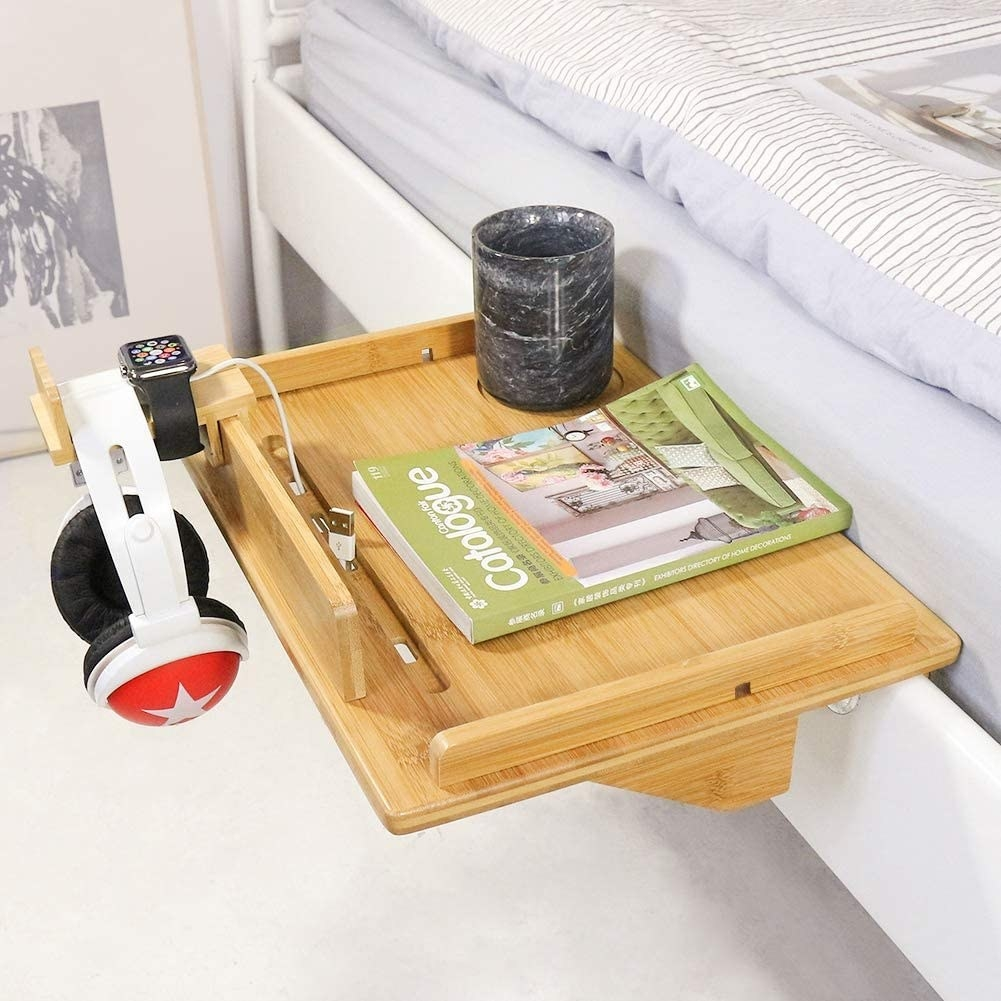 bedside caddy on the side of a bed with a glass of water, a book, and a headphone set next to an apple watch