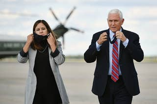 Mike Pence and his Karen Pence take their face masks off while walking on a plane tarmac