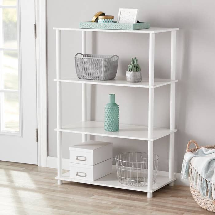 a white shelf system with four tiers holding decor and boxes in a room