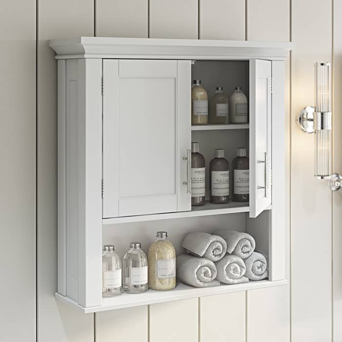a white bathroom cabinet with two doors and one shelf hung on a wall