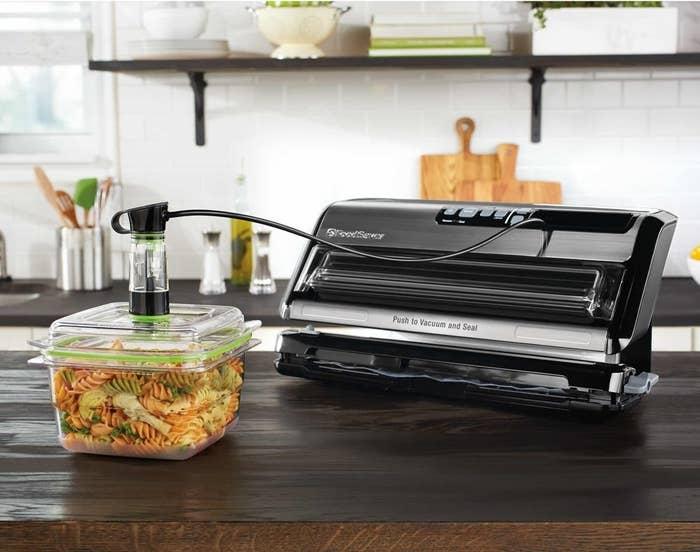 a black vacuum sealer sealing a storage container full of pasta