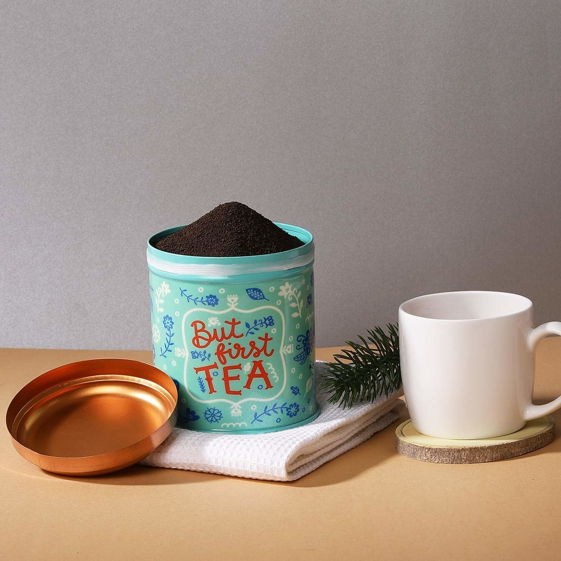 A teal coloured tin with a copper lid with doodles of leaves and flowers in blue and white and text in red that says 'But first tea.'