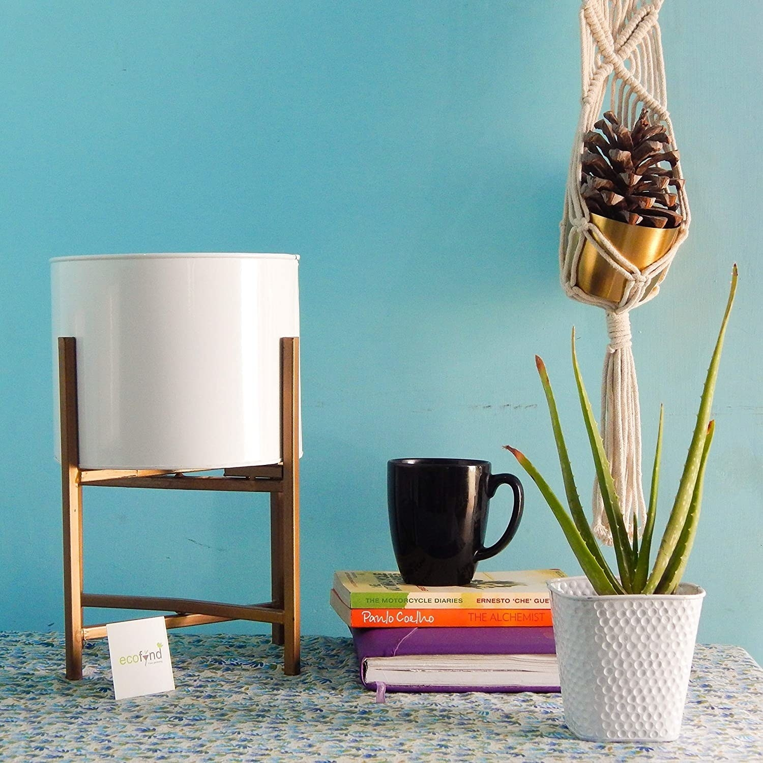 A round white planter atop a copper stand.