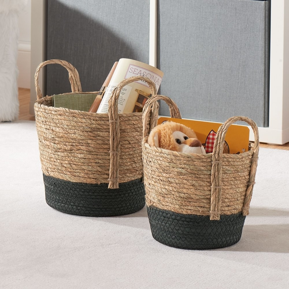 two storage blankets made of tan and black rope and seagrass with two handles holding books