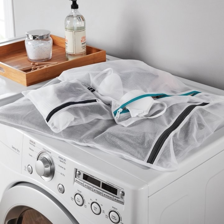 three mesh laundry bags on top of a dryer