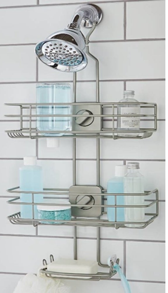 a brushed nickel shower caddy hung over a showerhead holding bottles on its two tiers and a soap bar in its soap dish tier