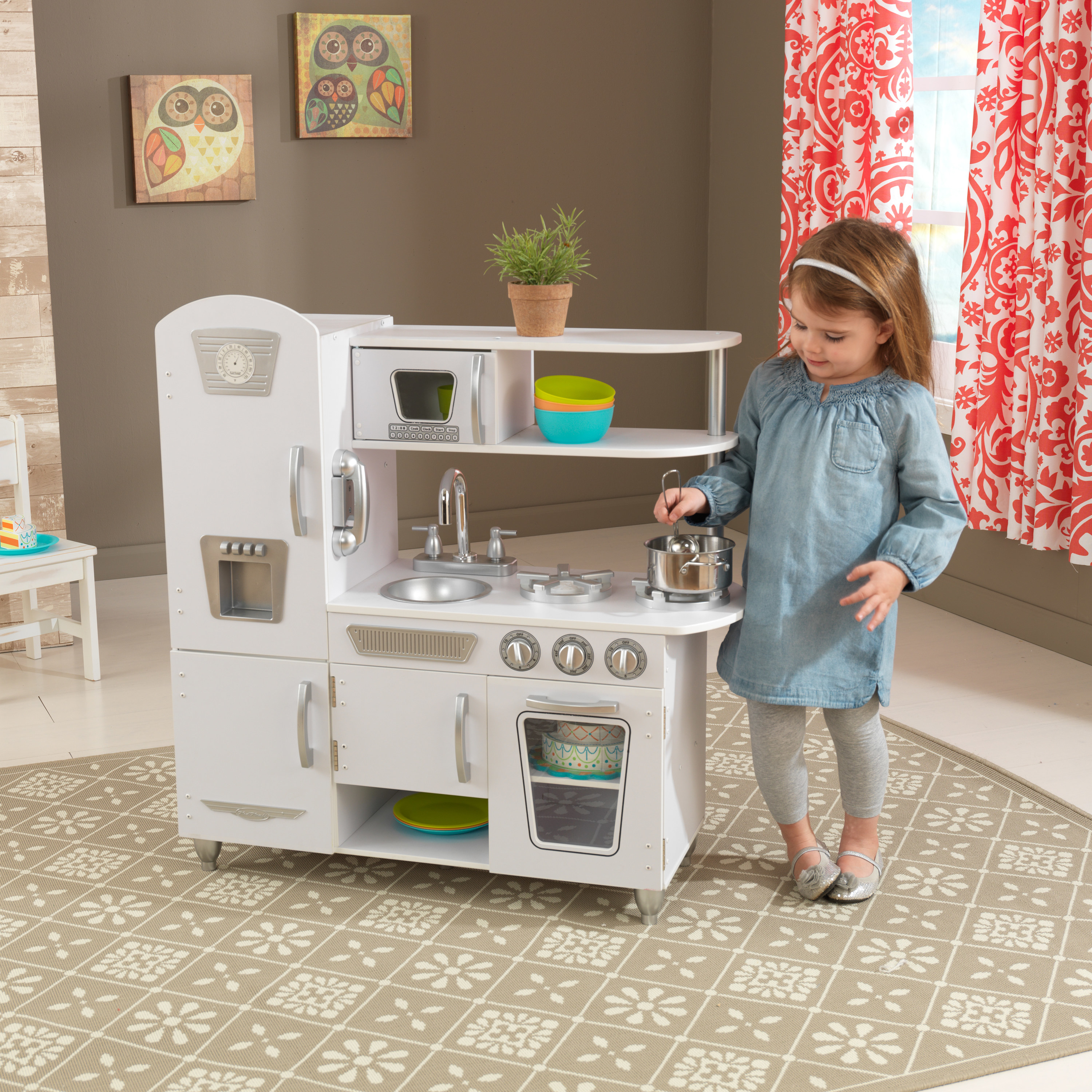 child plays with the pretend pots and pans in a play kitchen