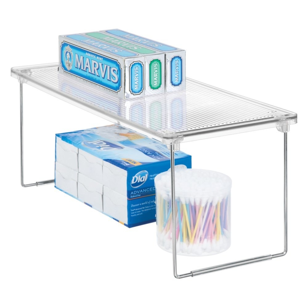 a clear acrylic shelf with two metal legs