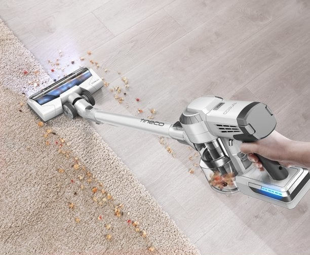 person using a tineco cordless vacuum to clean up crumbs on the floor
