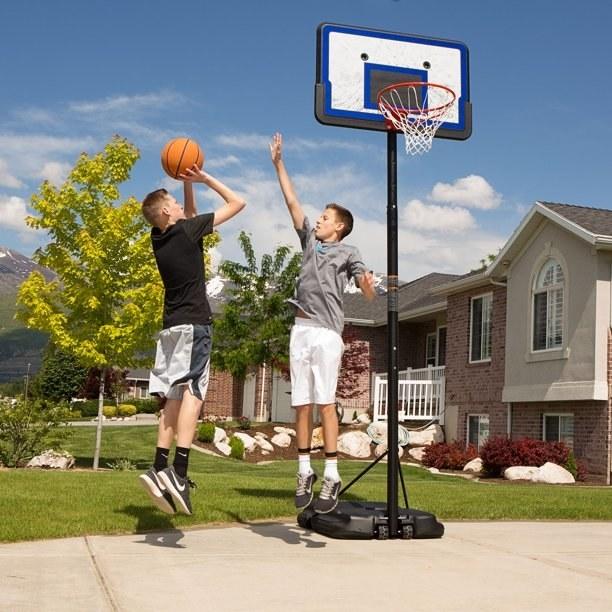 two teens playing basketball near a basketball hoop