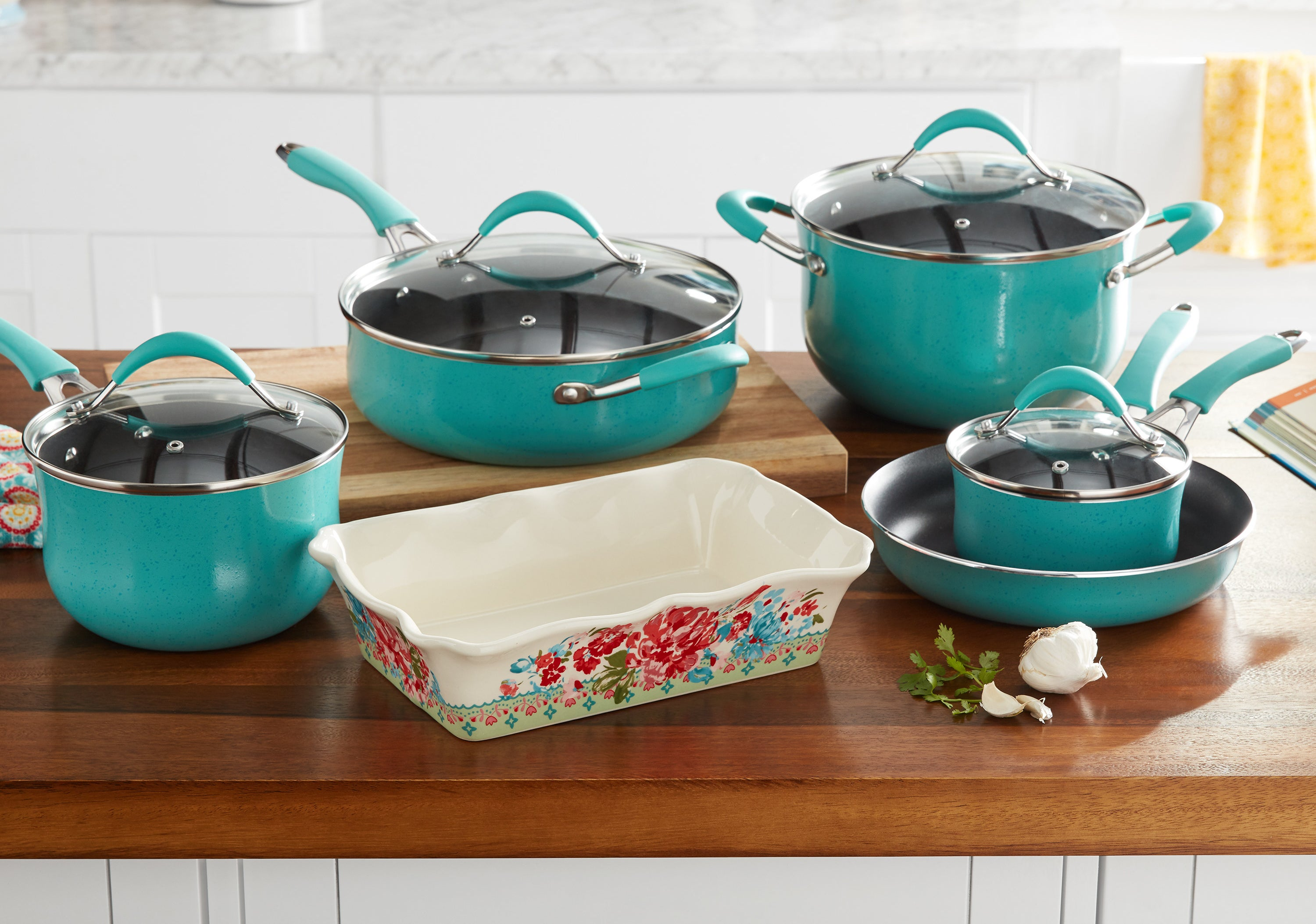 turquoise pots and pans and a floral casserole dish on the kitchen counter