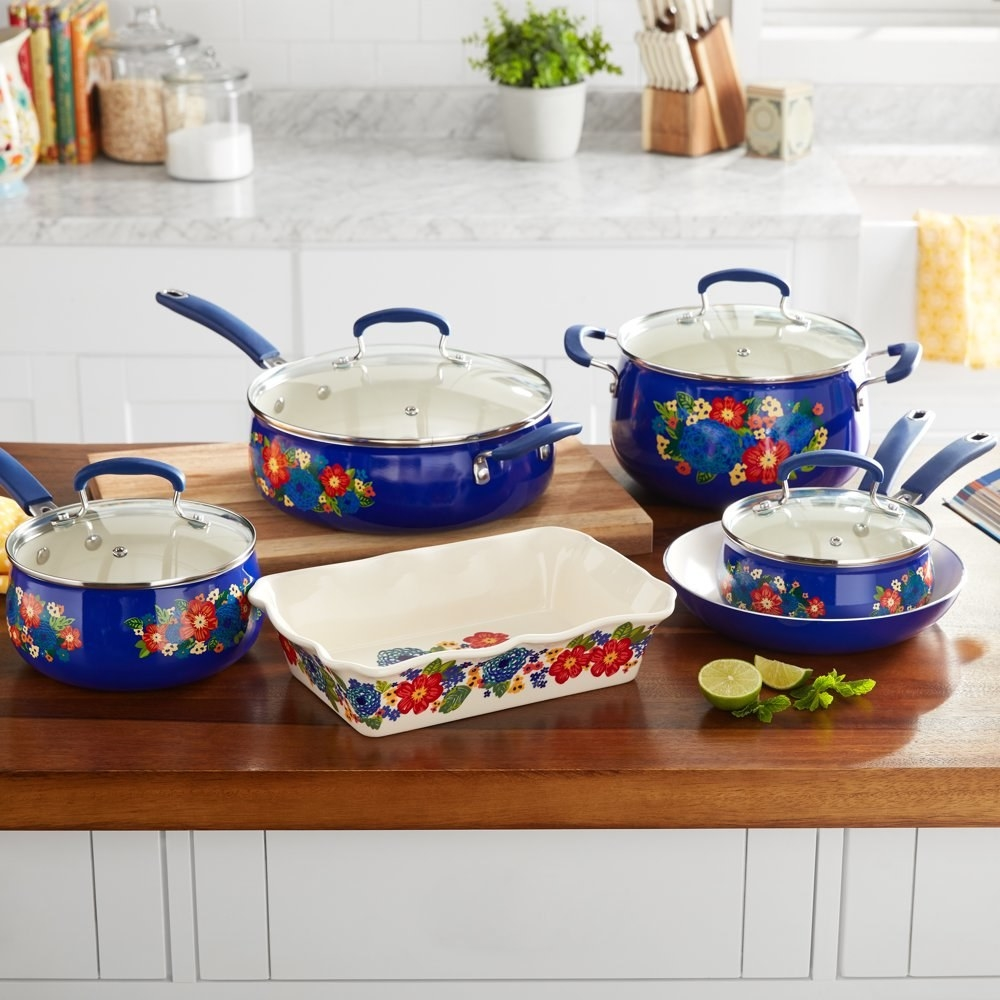 a set of blue pots and pans with red yellow and green floral designs on them