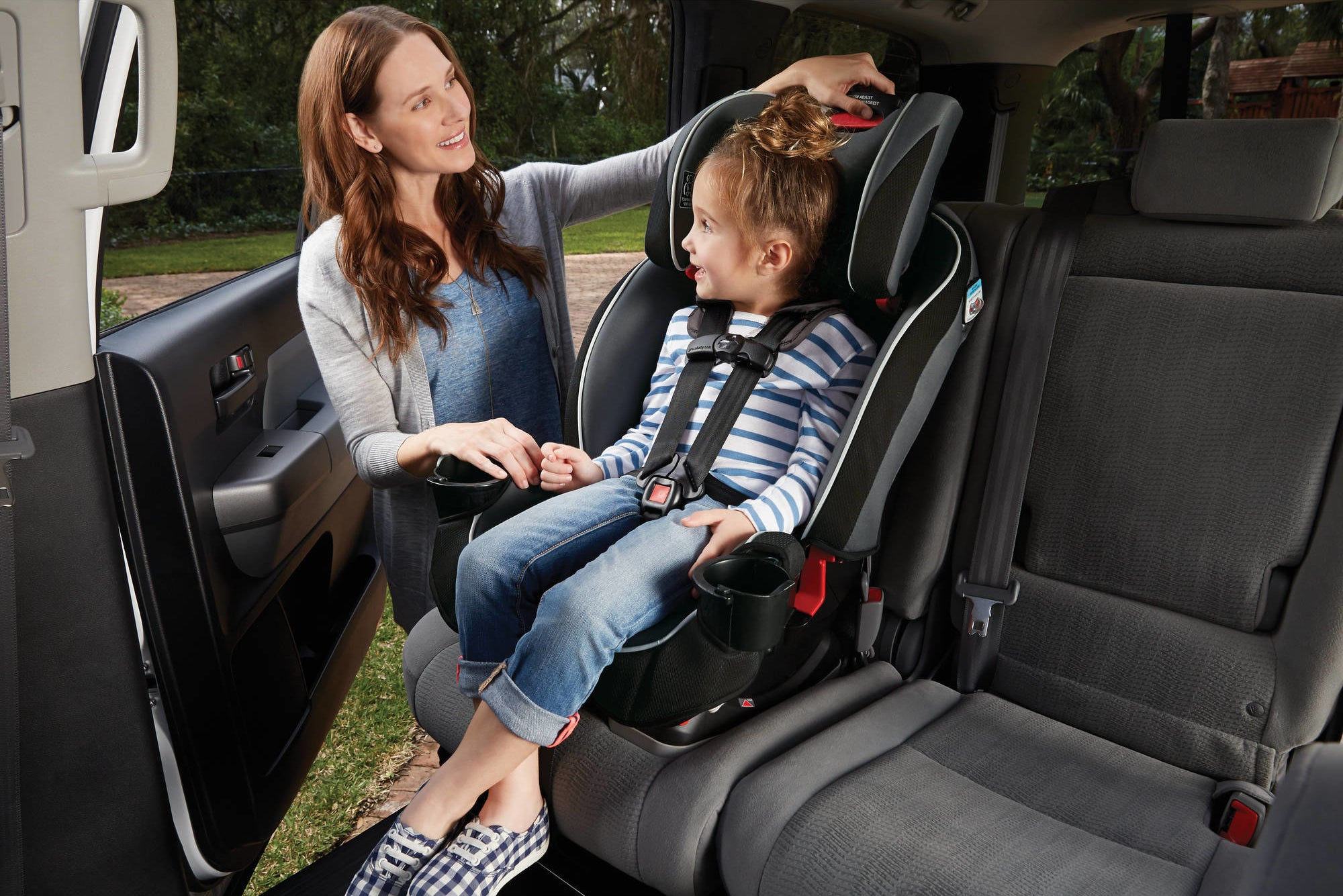parent adjusting a car seat with a child in it