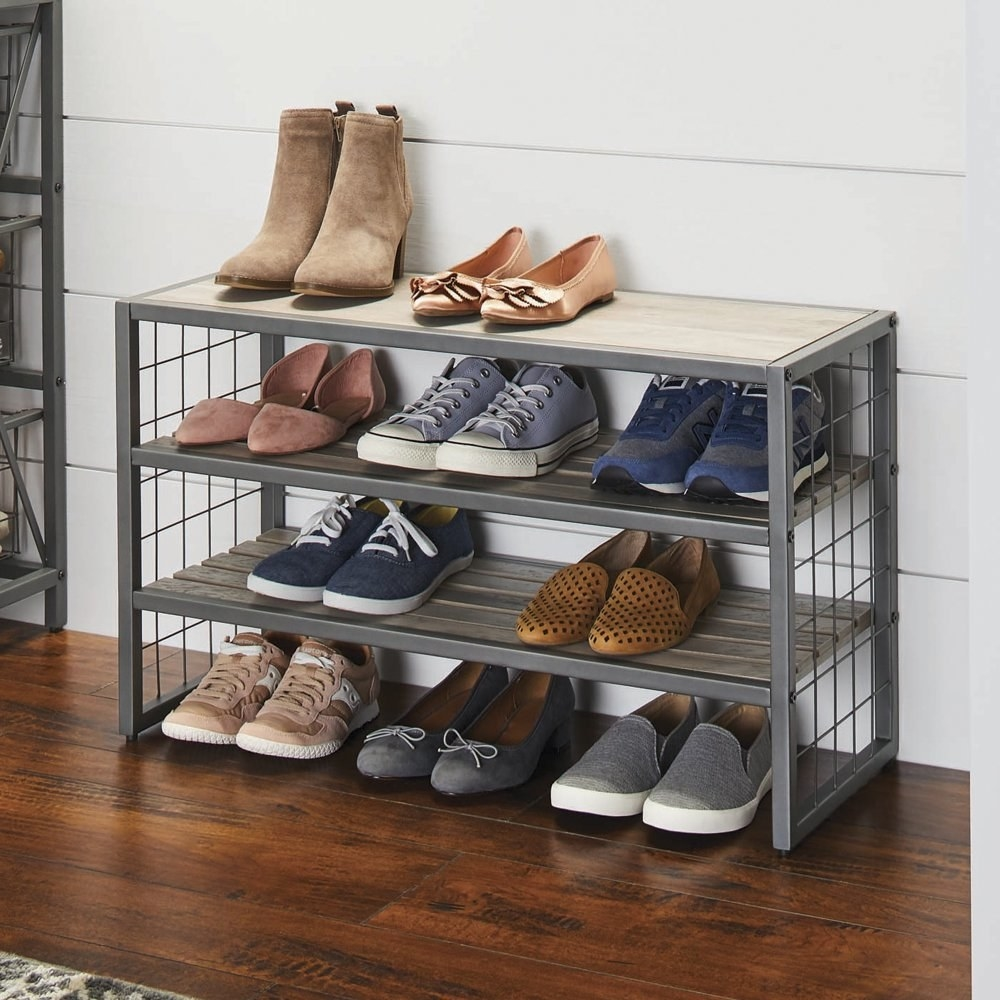 a wood and metal shoe rack holding pairs of shoes on three racks