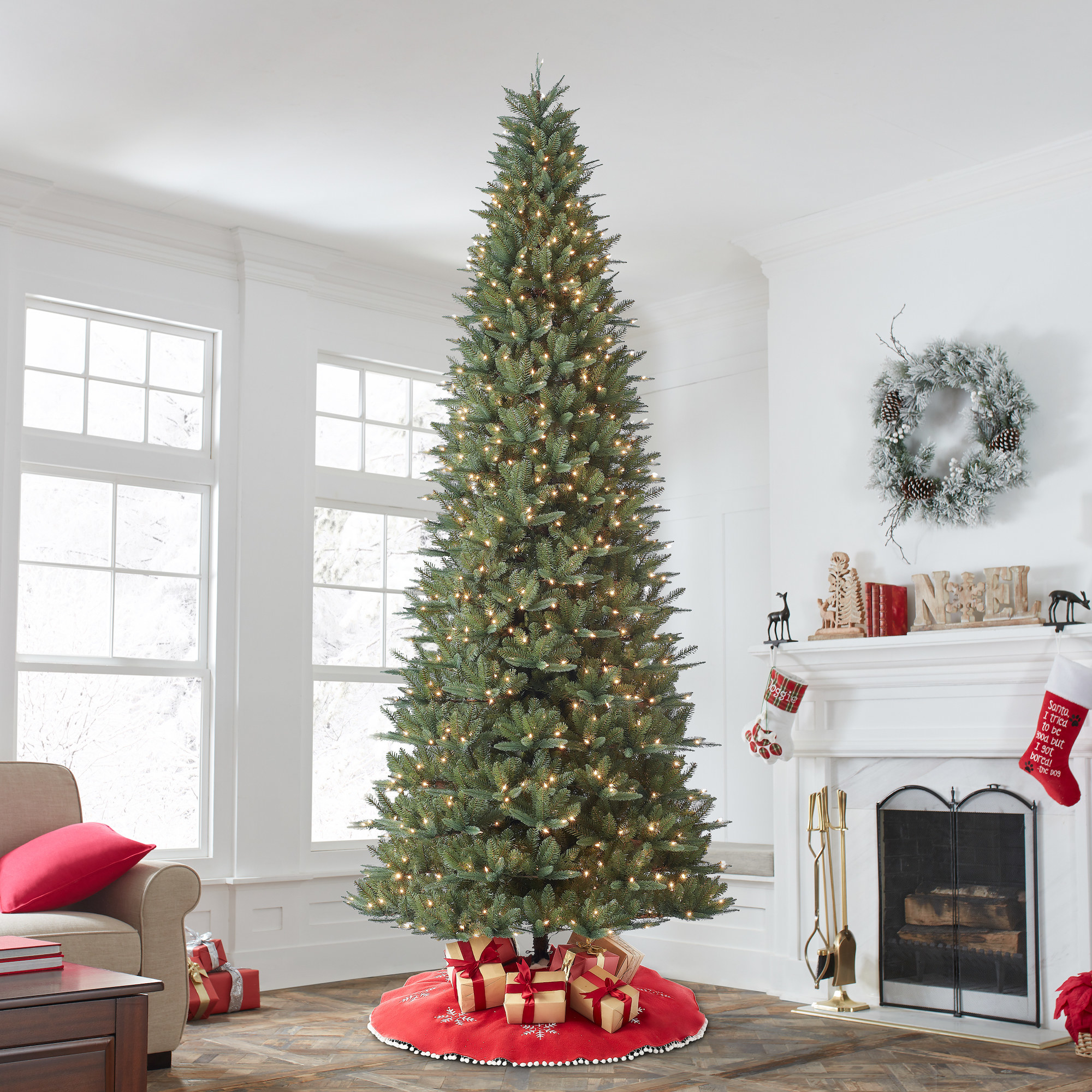 pre-lit artificial christmas tree with presents underneath it