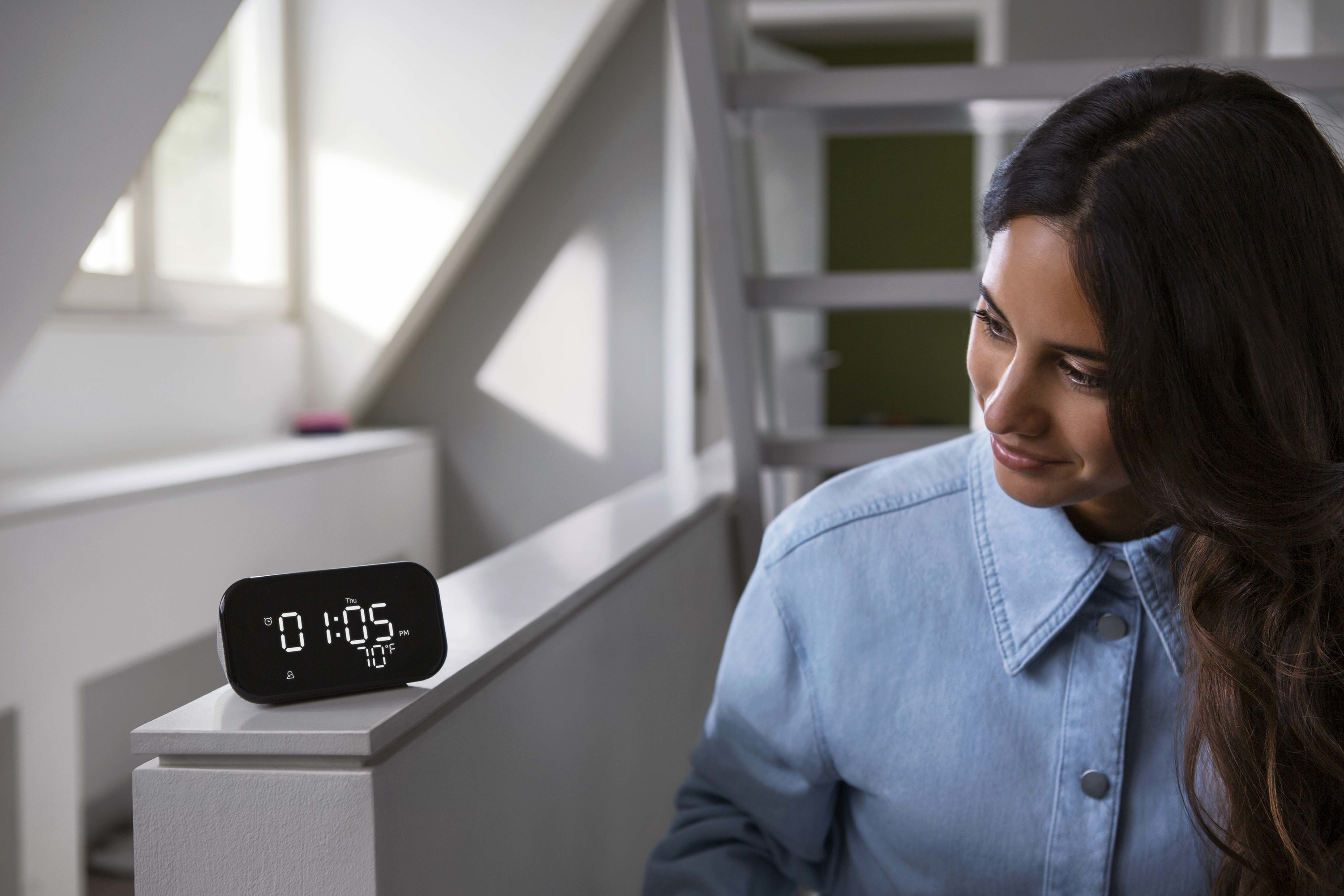 person looking at a lenova smart clock on a white ledge