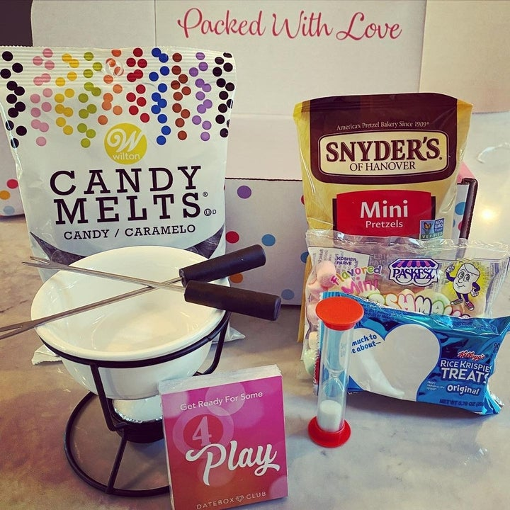 Candy melts, mini marshmallows, pretzels, and small fondue bowl with fondue forks and a tea candle