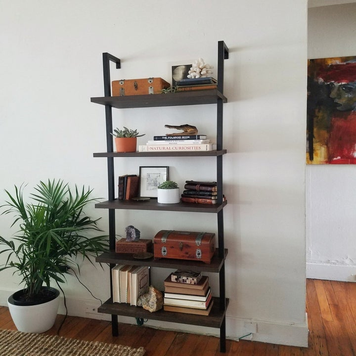 A reviewer's bookshelf in warm walnut and black