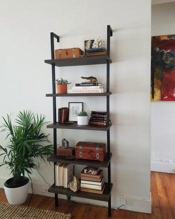 A reviewer's photo of the bookshelf in warm walnut and black
