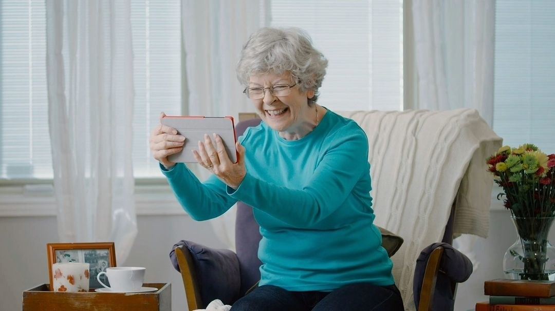 Older person holding the tablet and smiling