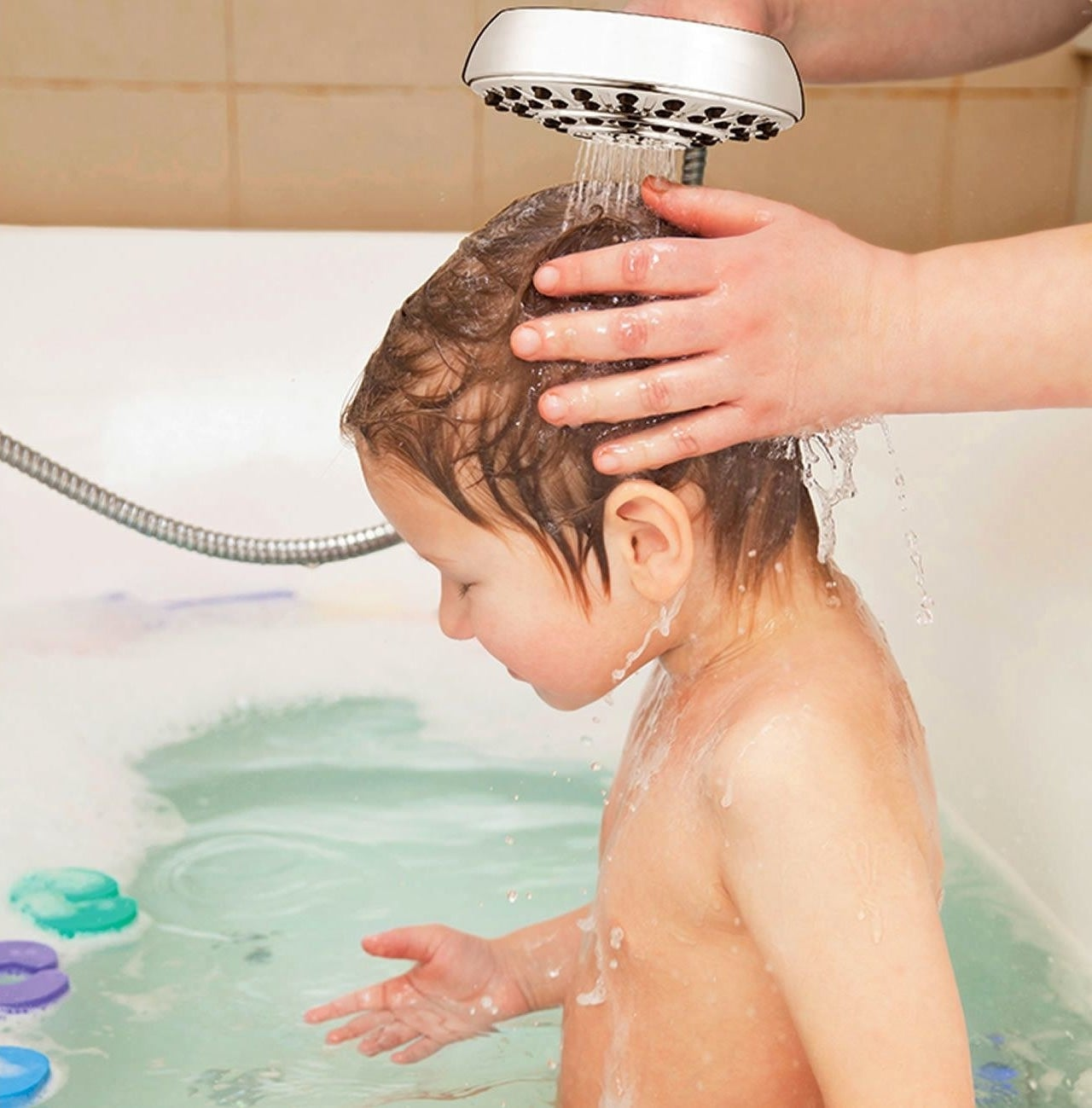 Child being bathed with shower head