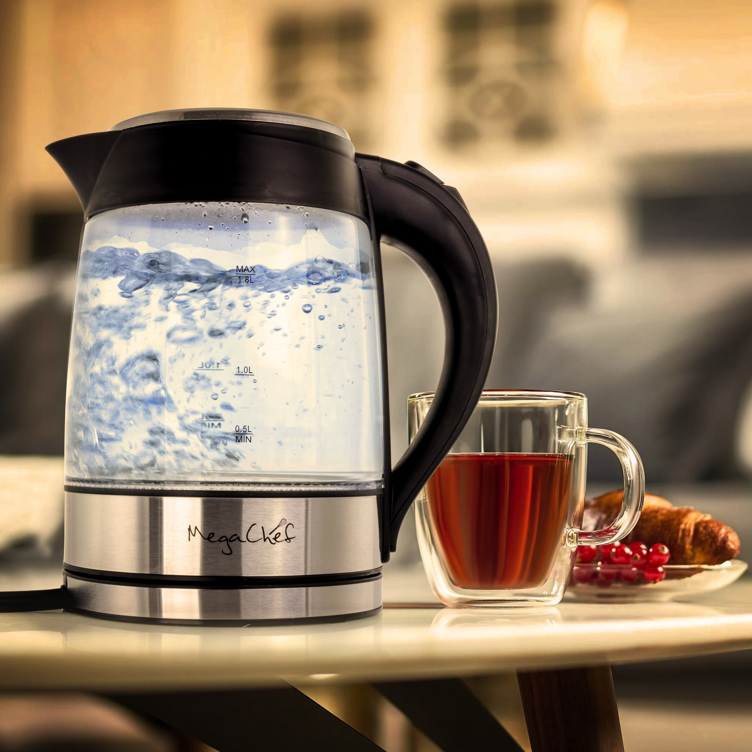 a glass and stainless steel electric kettle boiling water next to a cup of tea