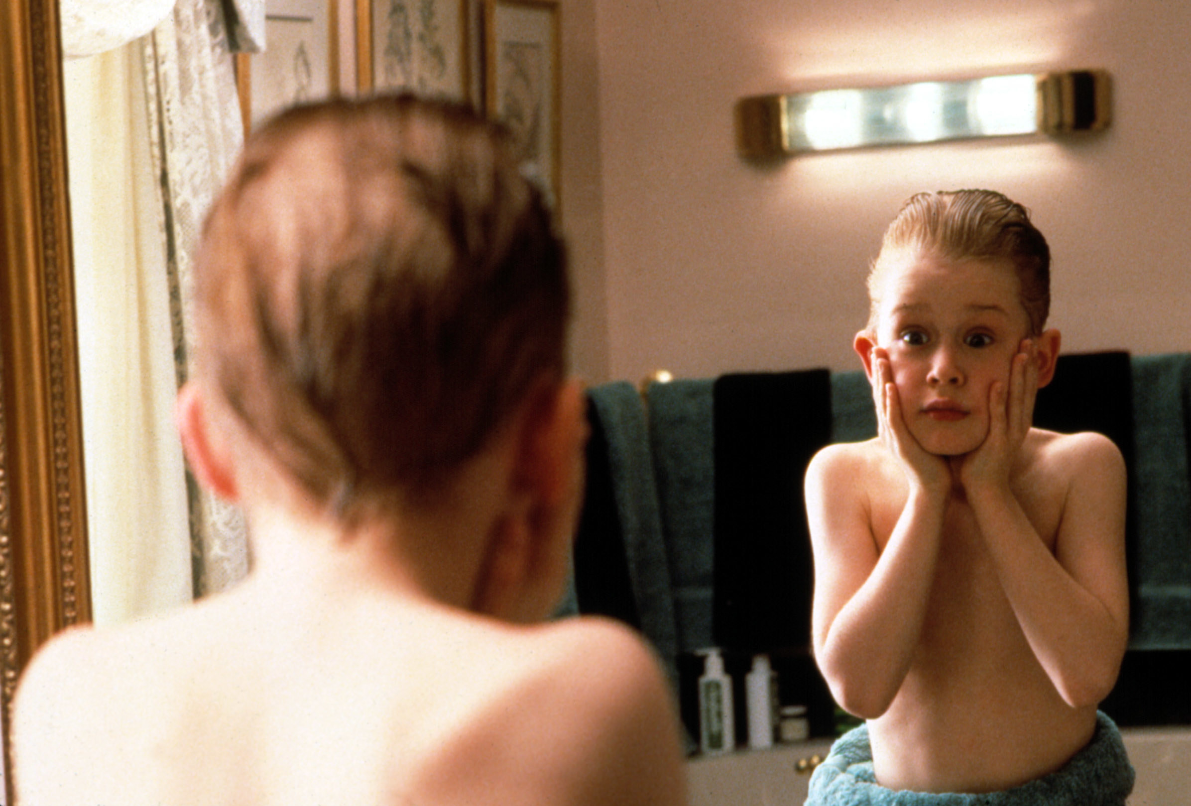 """Kevin McCallister in """"Home Alone"""" holds his face in shock as he looks in a mirror"""