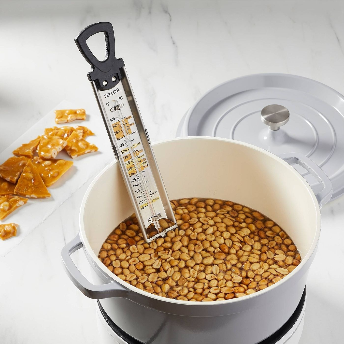 the taylor candy thermometer in a pot full of peanuts.