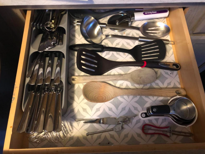 reviewer photo showing silverware organizer on the left of a drawer with plenty of room for other utensils on the right