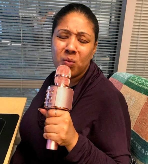 A reviewer using the pink karaoke mic