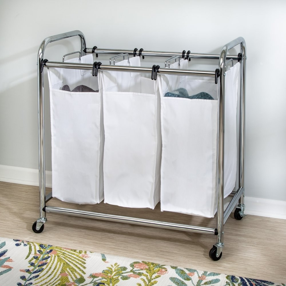 a laundry basket on wheels with three white fabric compartments supported by a chrome frame