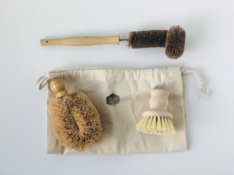 a dish scrubber with a wooden handle, a glass brush with a wooden handle, and scrub brush with a wooden handle and plant fibers
