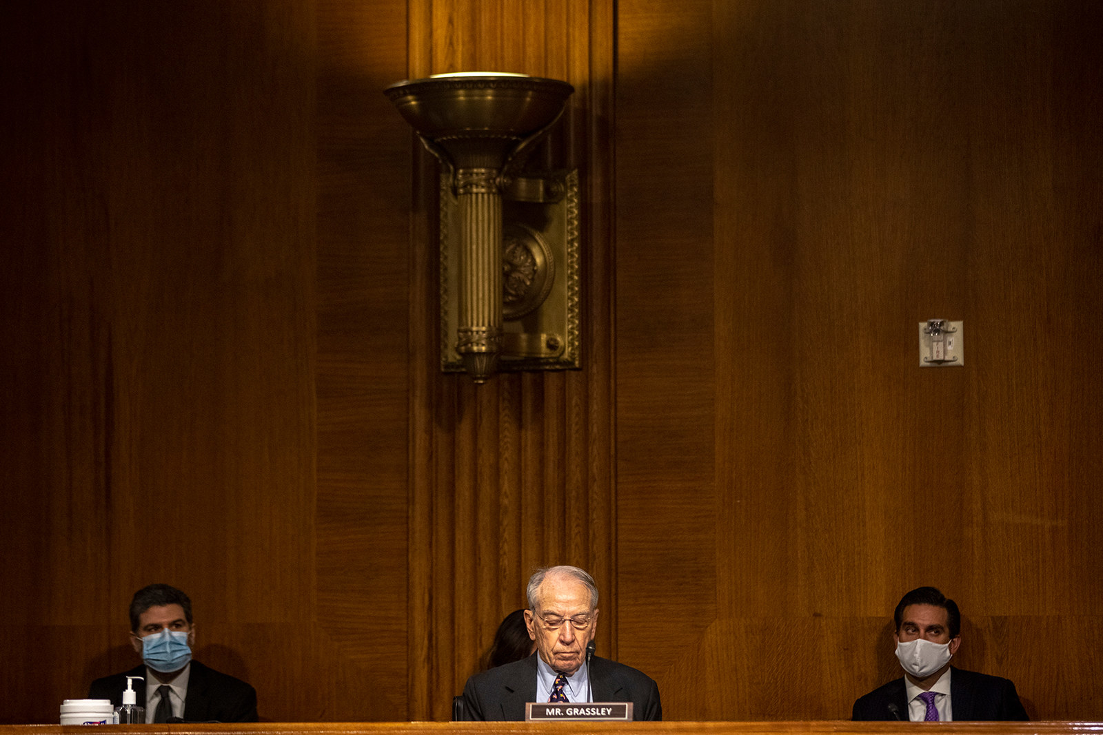 "Three men sit behind a long bench with Senator Chuck Grassley at the center sitting behind a placard that reads ""Mr Grassley"""