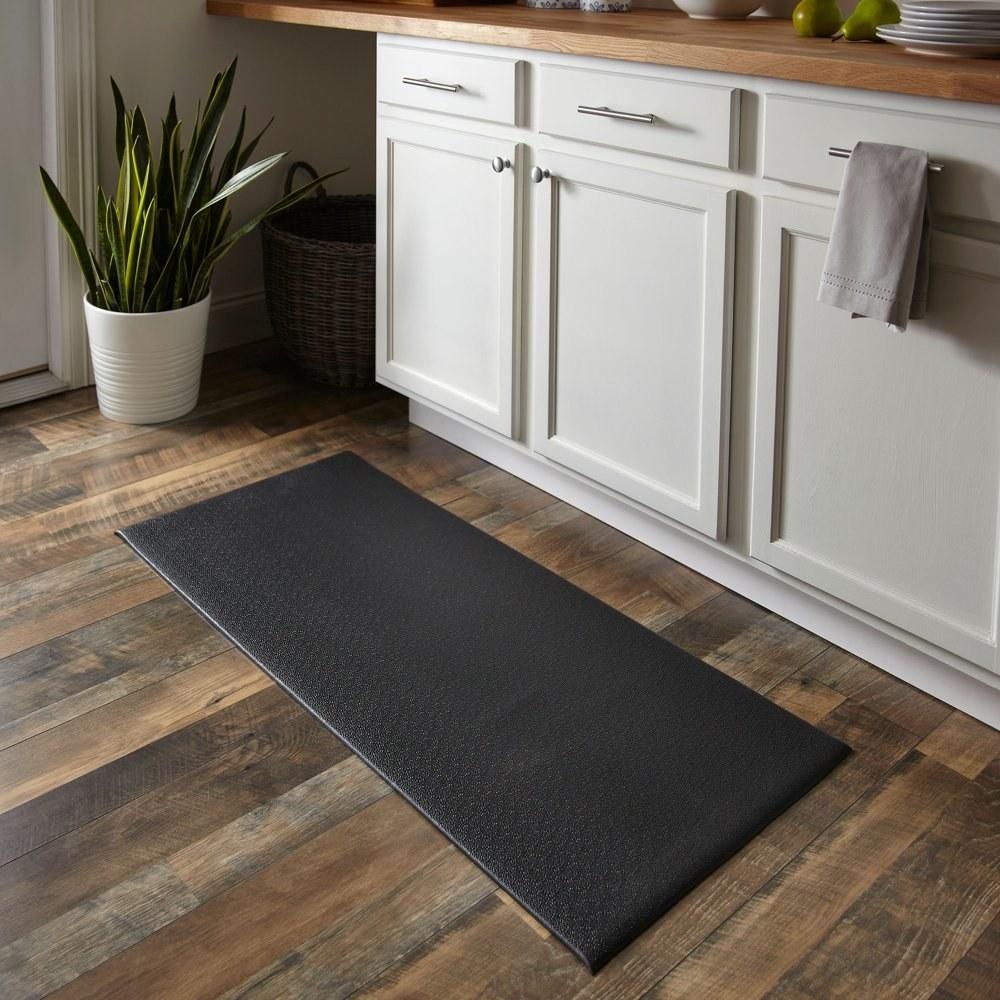 a black rectangular floormat in a kitchen