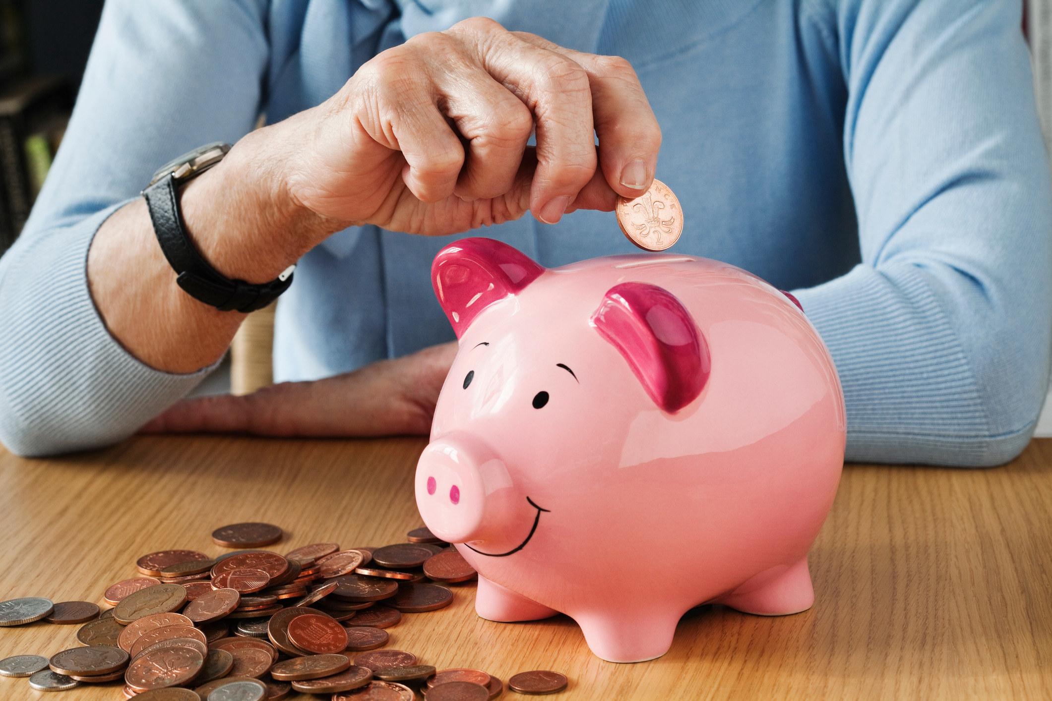 Person putting money into a piggy bank