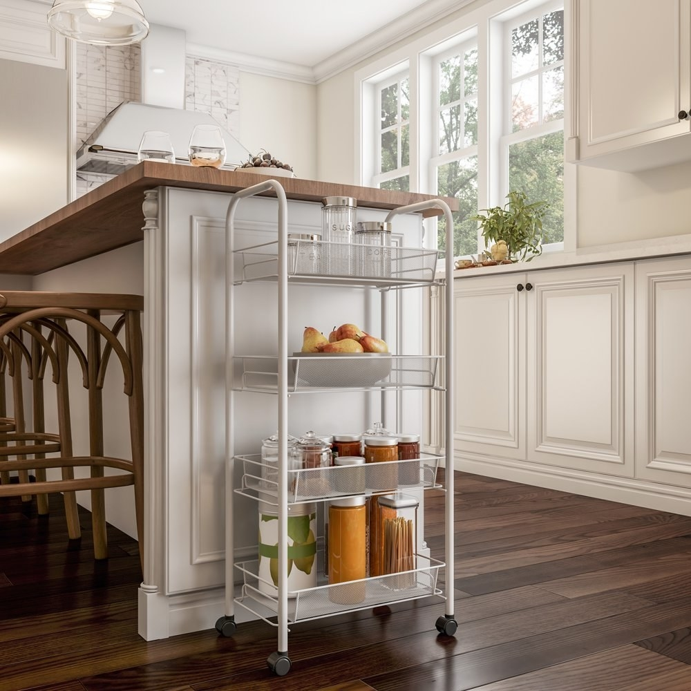 a 4 tiered rolling cart holding pantry essentials next to a kitchen island