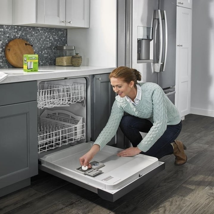 A person putting a tablet into their dishwasher