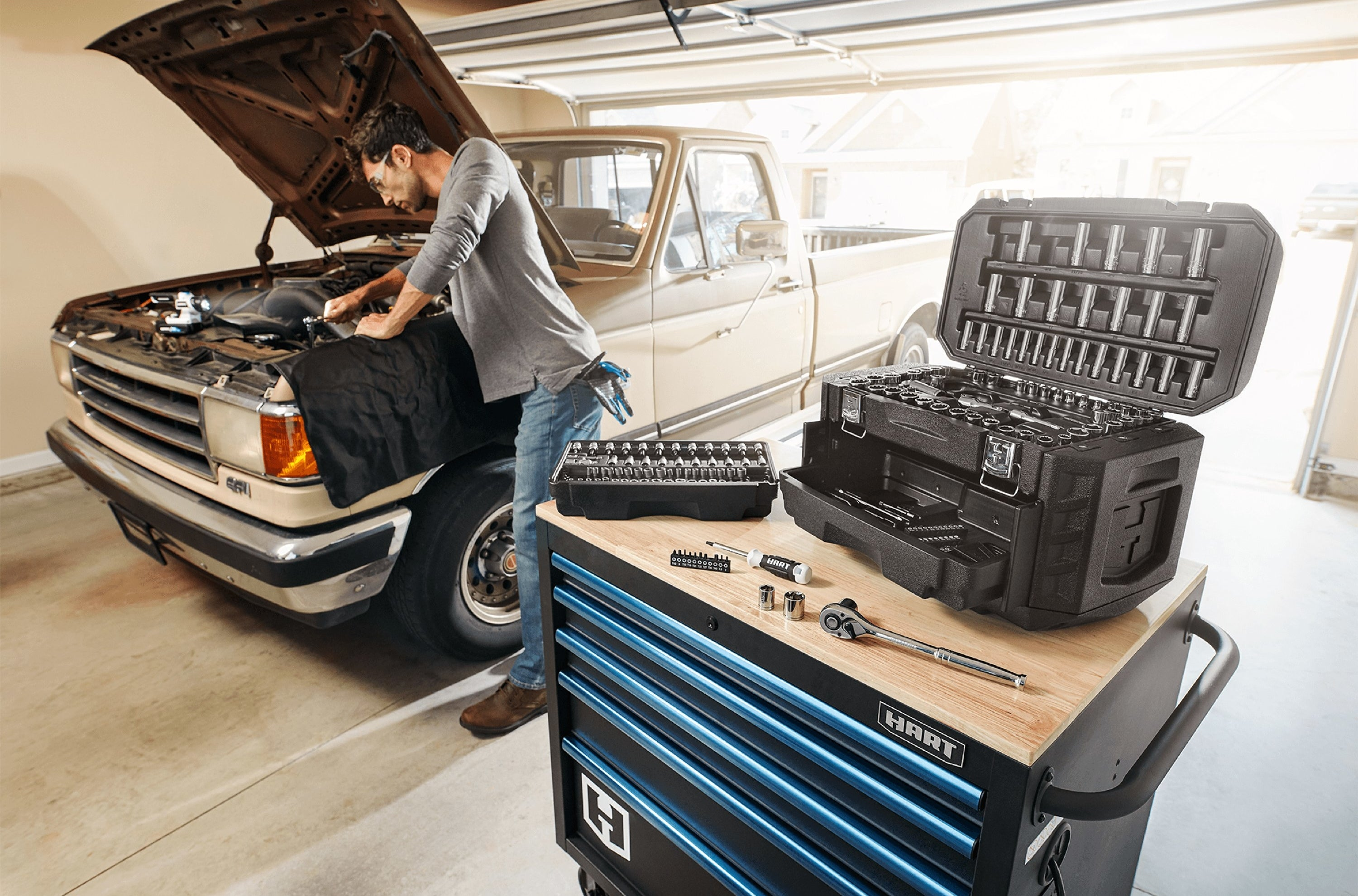 black tool kit with 215 pieces in the foreground with a person working on their car in the background