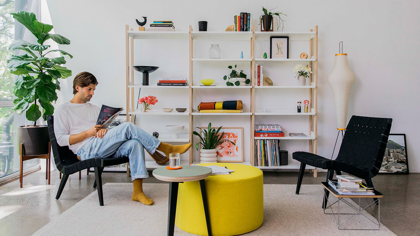 a model sitting in their living room with the modern shelving in white and tan behind them