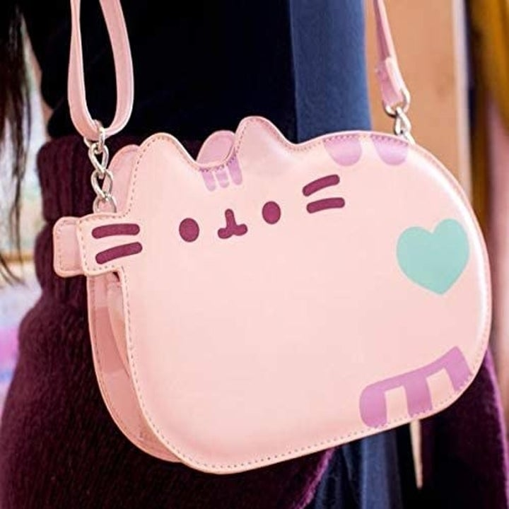 A model carrying the pink bag shaped like a loafing Pusheen with a green heart on her butt